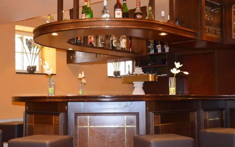 Close up of the bar wooden area with bar stools