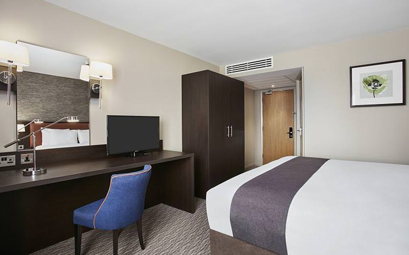 A double bed in a hotel room, facing a large wooden desk with blue chair, TV and wardrobe
