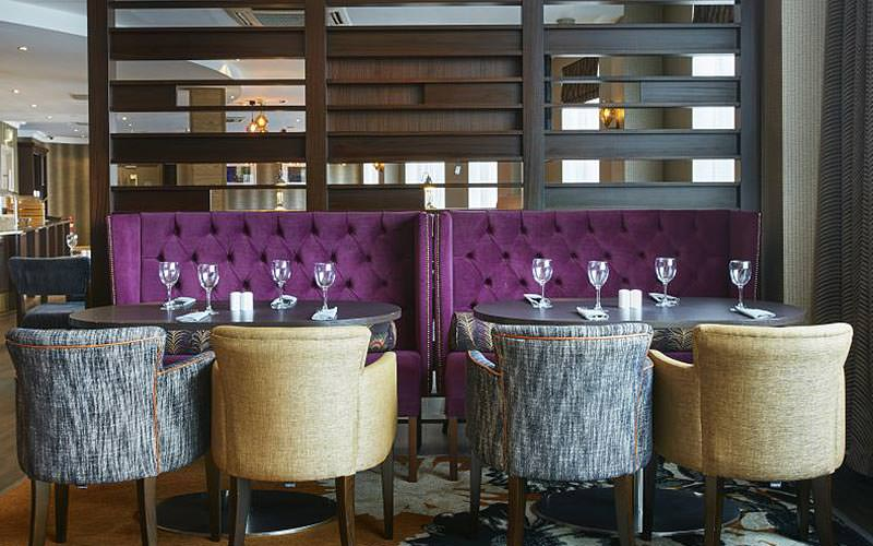 Two purple booths set for dinner in the Holiday Inn Belfast City Centre restaurant