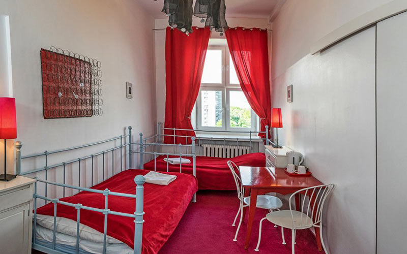 A red and white room with beds, a desk and chair