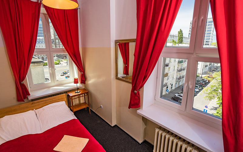 A red ad white room with two windows and a bed