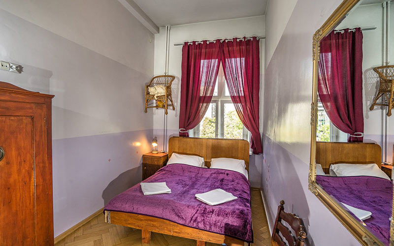 A white walled room with a white and purple bed