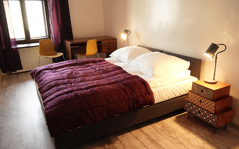 A room with a white and purple double bed, with bedside tables