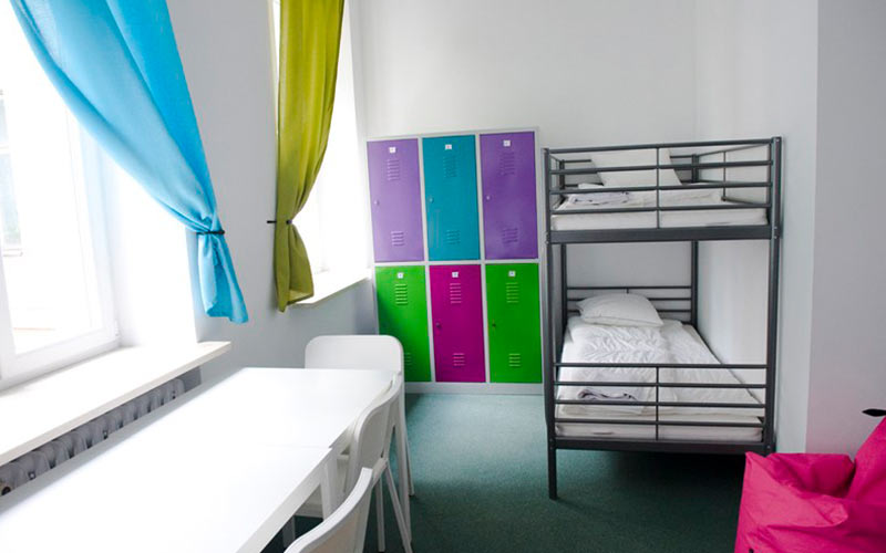 Bunk beds and a table and chairs in a room, with lockers in the background