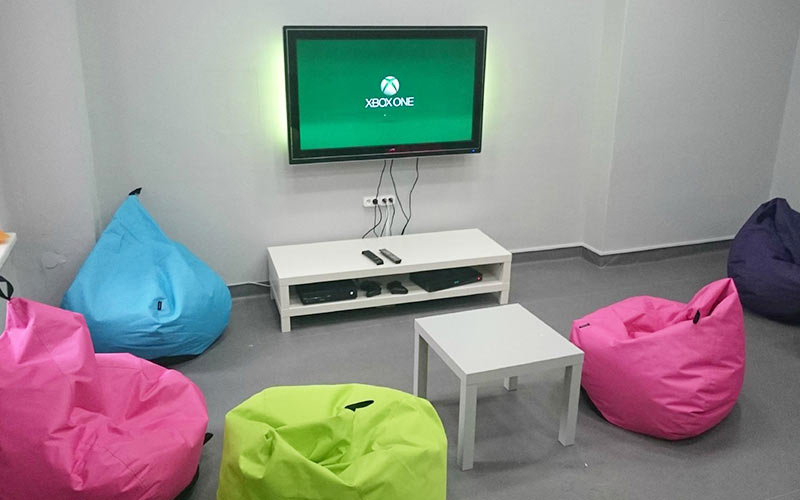 A TV mounted on the wall, connected to an X-box, with multicoloured bean bag chairs on the floor
