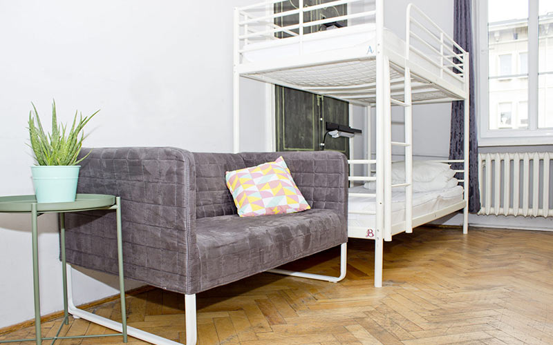 A white waled room with bunk beds and a sofa