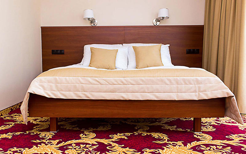 A large bed in a hotel room with a red and yellow carpet