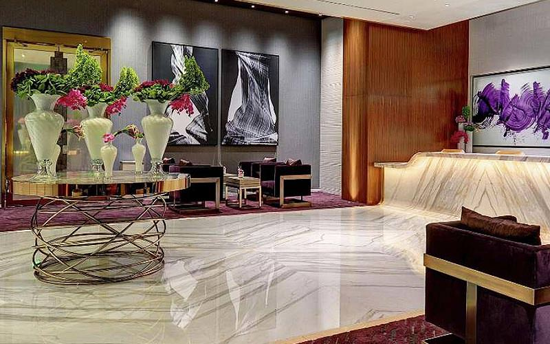 A marble floored lobby with artwork on the walls and an intricate, flower covered table
