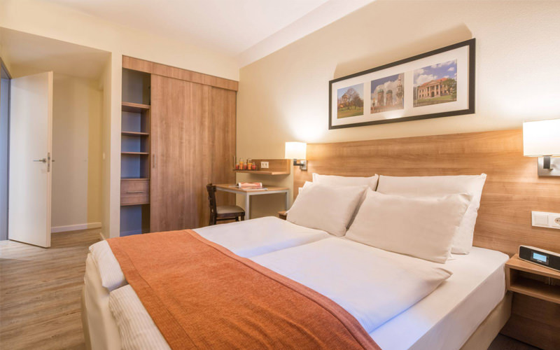 A double bed with an orange throw and wood based furniture
