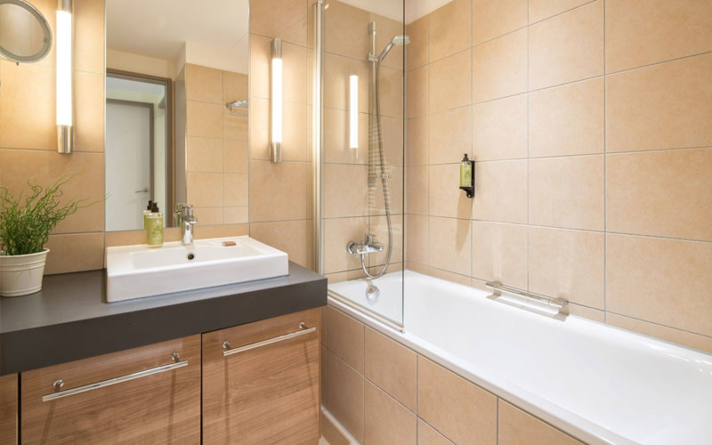 A view of a modern bathroom with a bath, built in shower and a sink