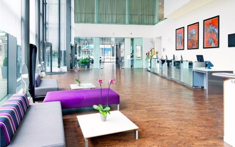Image of reception desk with wooden flooring and huge full length windows with purple seating and a white table with a purple orchid plant