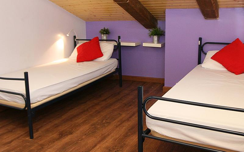 Two single bedstopped with red cushions in a pruple room