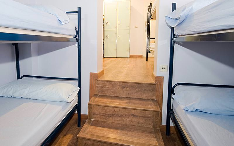 Two bunk beds in a room with a small staircase in the middle of them