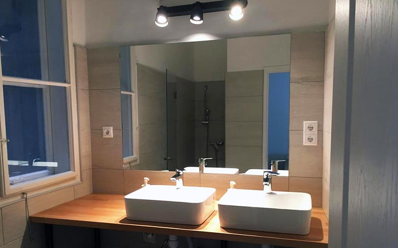 A bathroom with two sinks and a large mirror
