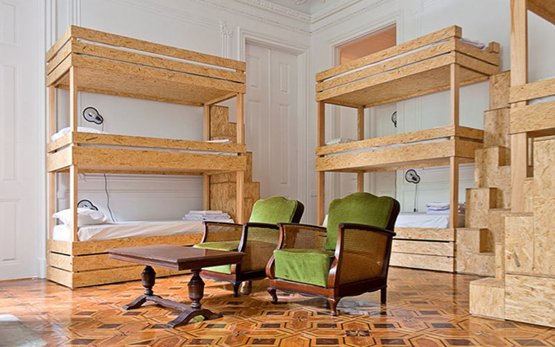 Some modern wooden bunk beds in a white walled room, with a table and chairs in the middle