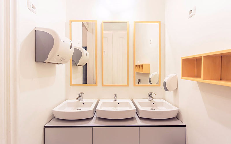 A white bathroom with 3 sinks and mirros
