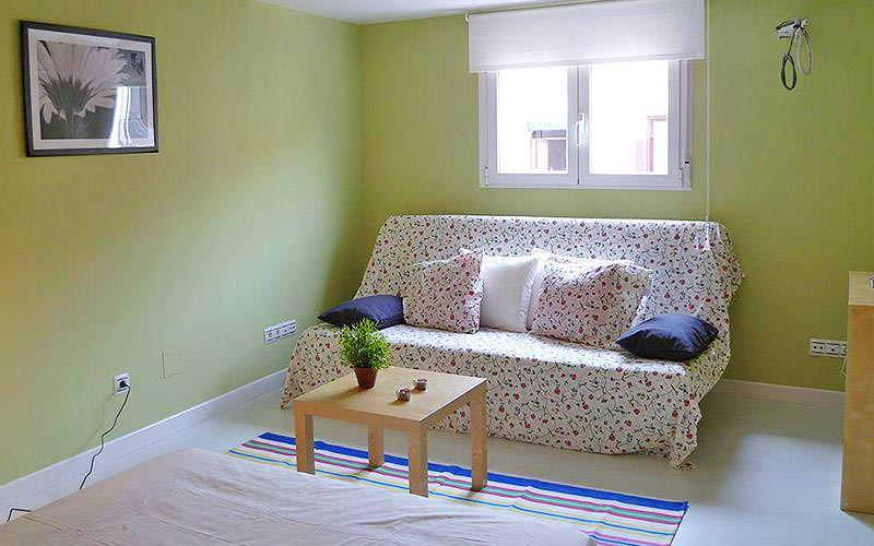 A dotted sofa in a green living area, facing a coffee table topped with a plant