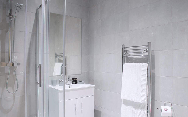 A neutrally decorated bathroom with a shower and heated towel rail