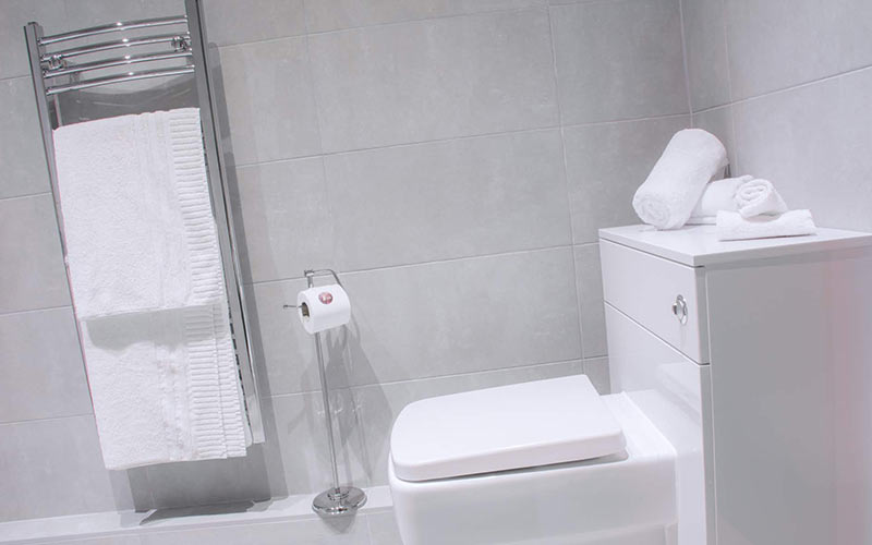 A neutrally decorated bathroom with a toilet and heated towel rail