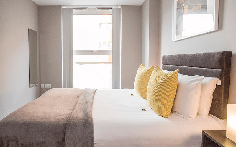 A light room with a black and white double bed and some furniture