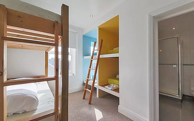 A dorm room with a wooden ladder resting on the wall