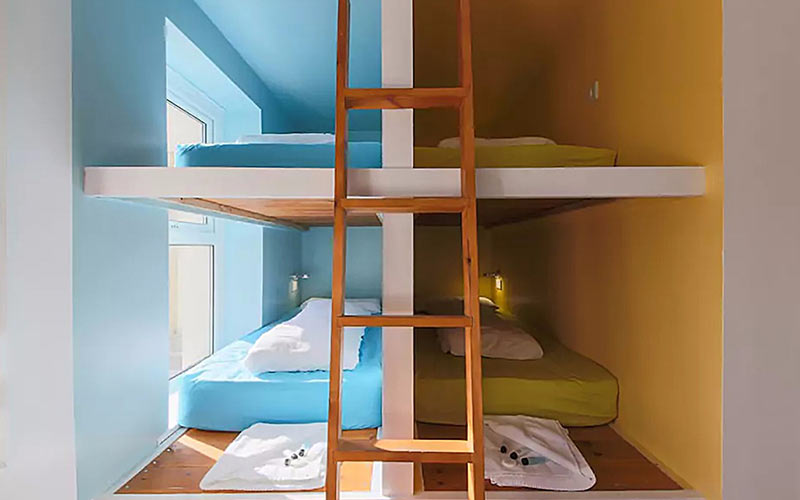 A ladder resting on the wall separating two bed spaces