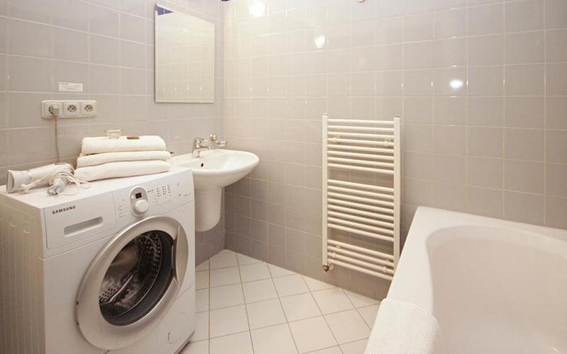 A bathroom with a heated towel rail, washer and bath