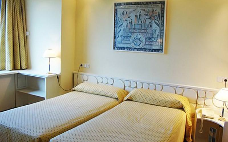 Two single beds in a hotel room with bedside tables topped with lamps on each side, and a picture above the beds