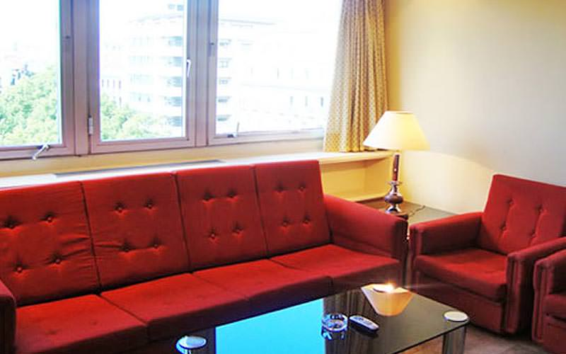 Red sofa and red chair around a table, with a lamp on a table in the back