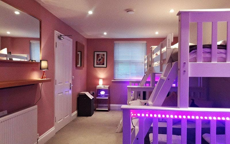 Some bunk beds in a bedroom, illuminated by purple