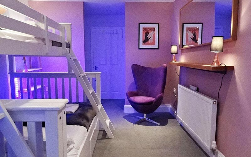 A dimly lit room with white bunk beds
