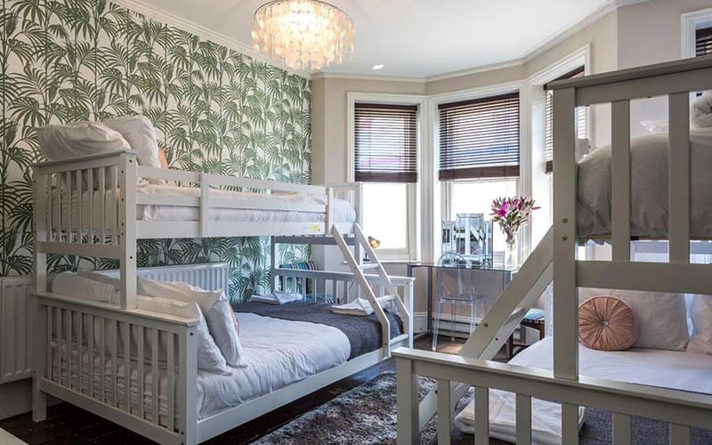 Image of two white wood bunk beds with a green leaf feature wall with a big bay window