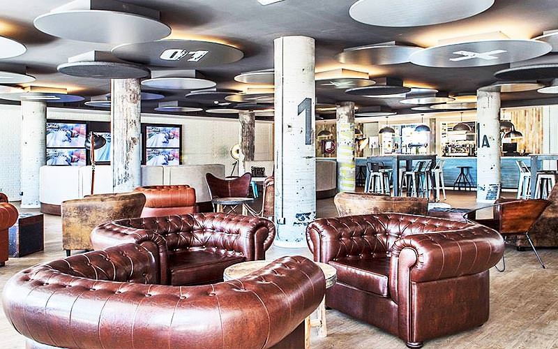 Brown leather sofas dotted around a room, with stools and tables in the background