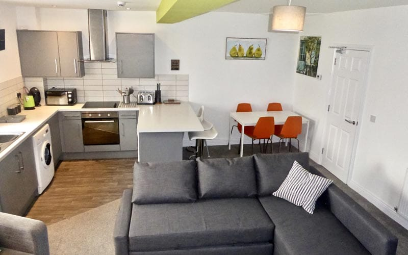 Image of a room with kitchen appliances and cupboards and a white dining table with four orange chairs and a grey fabric corner sofa