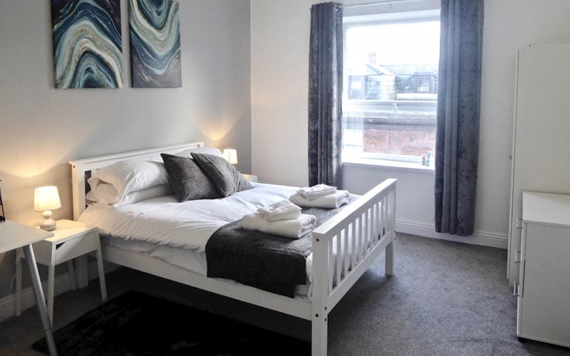 Image of a room with a white wood double bed and a window with grey curtains with white furniture
