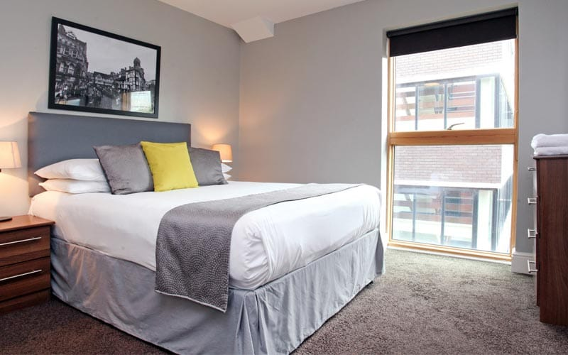 Image of a room with a double bed with a grey bed runner and grey and yellow cushions with a big window with a picture above the bed