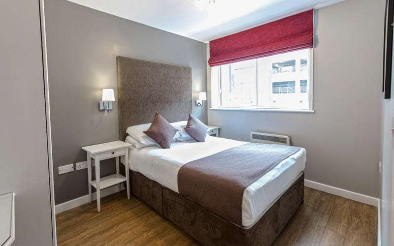 Image of a room with a double bed with a big headboard and wooden flooring and a window with a red roller blind