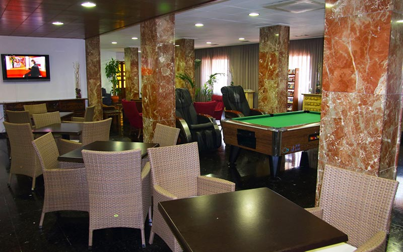 A lobby with tables and chairs and a pool table