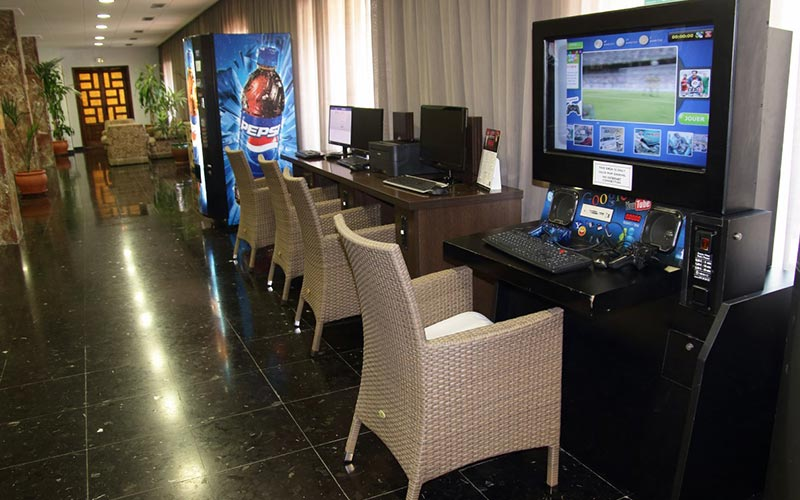 A line of desks and chairs with TVs and games consoles