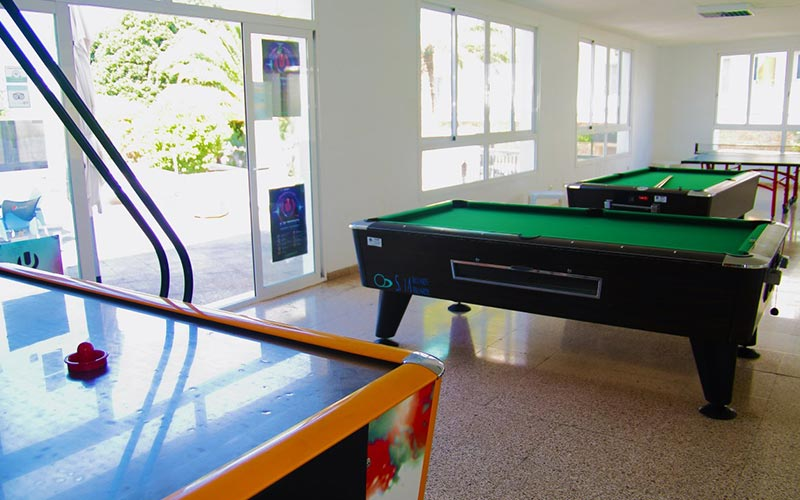 A room with two pool tables and an air hockey table