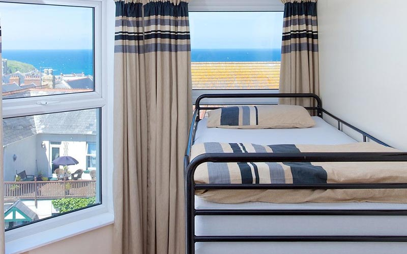 Bunk beds in a white walled room with a window in the background and a view of the sea