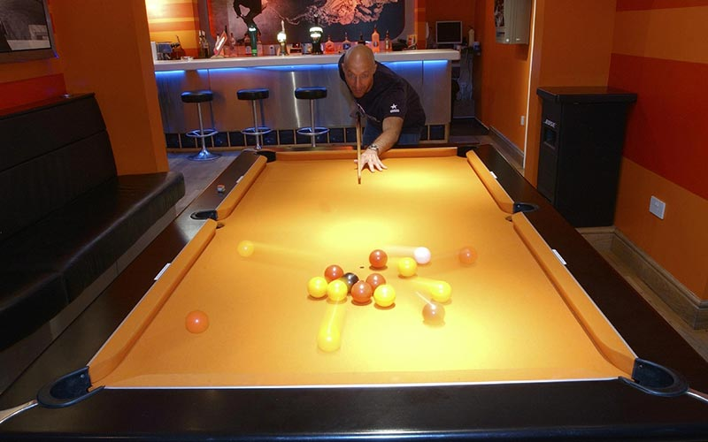 A man playing pool with a bar in the background
