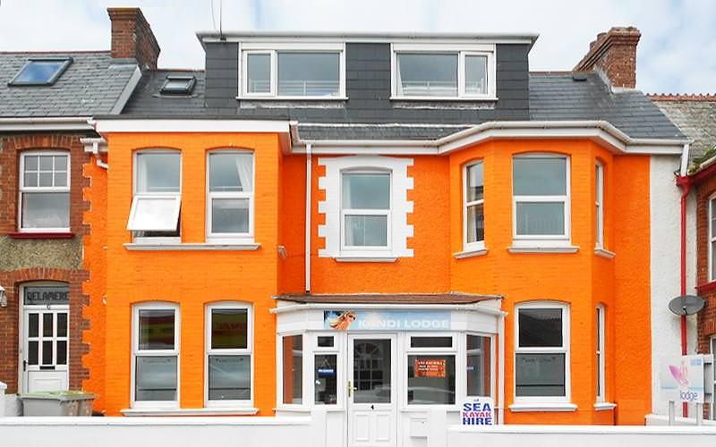 The orange exterior of Kandi Lodge hostel