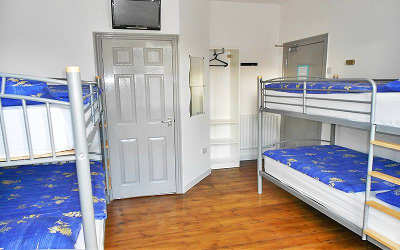 White bunk beds with blue duvet covers in a room at Kandi Lodge Hostel