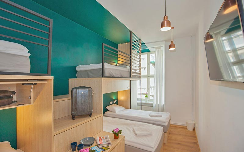 A guest bedroom at Draggo House with turquoise walls and a TV mounted on the wall