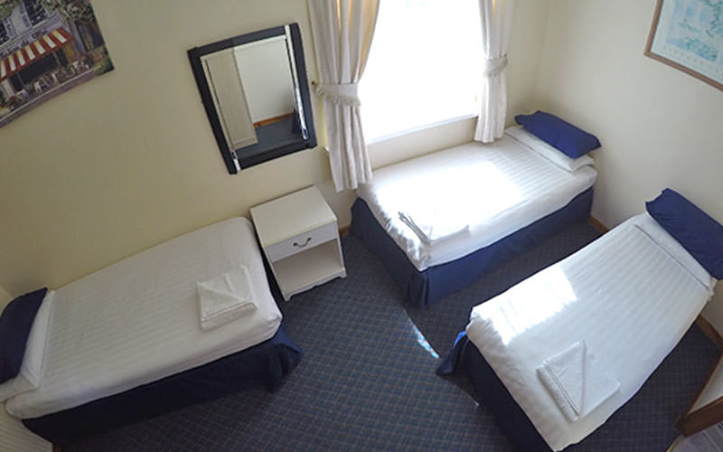 Three single beds in a blue hotel room