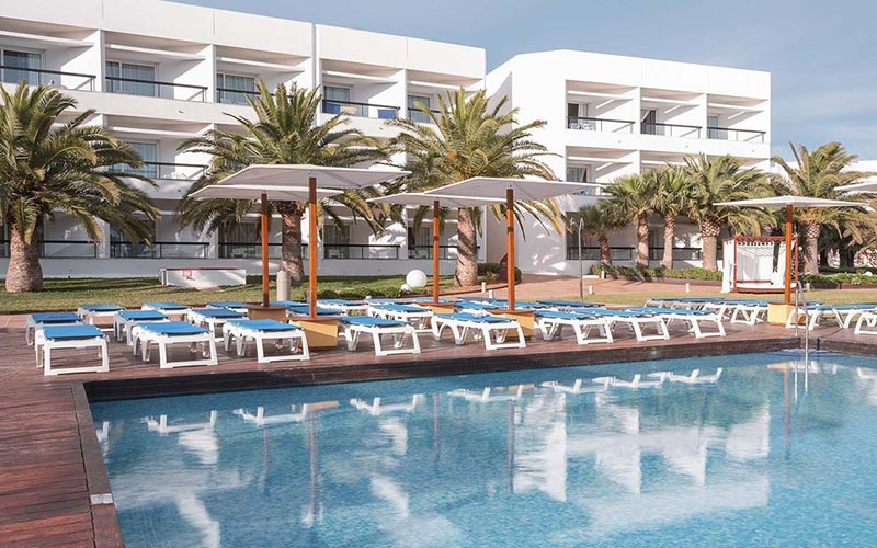 The exterior of Palladium Palace Ibiza with a large swimming pool and sun loungers