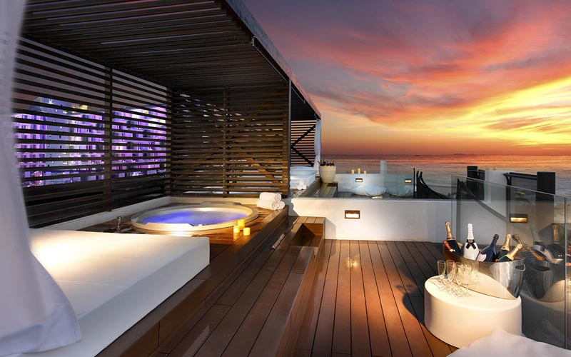 The Rock Suite Platinum with an outdoor hot tub with the sunset in the background
