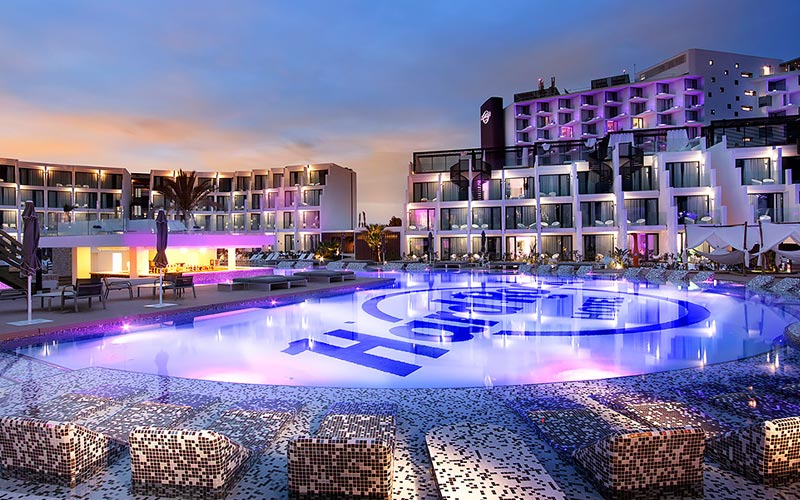 The exterior of Hard Rock Hotel, lit up and splash pool