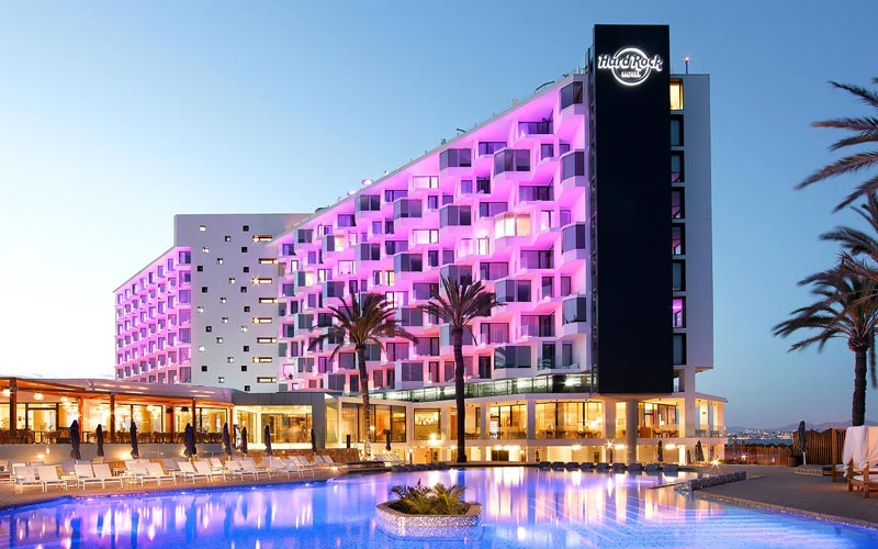 The exterior of Hard Rock Hotel, lit up and the Eden pool